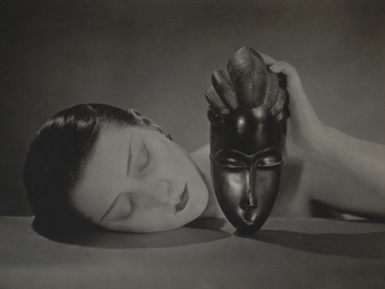 b&w photo of a white woman posing as asleep while holding an African mask