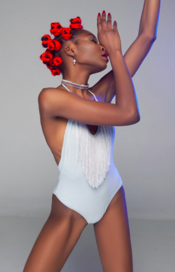 a young woman in a white leotard is posed dramatically with eyes closed