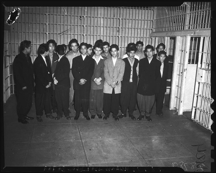 18 young men stand in a jail cell, wearing Zoot suits and other dressy attire