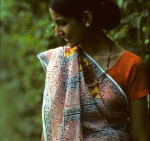 A portrait of a woman in a sari standing in front of lush trees