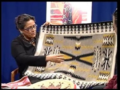 Woman holding a Navajo rug and pointing to its designs