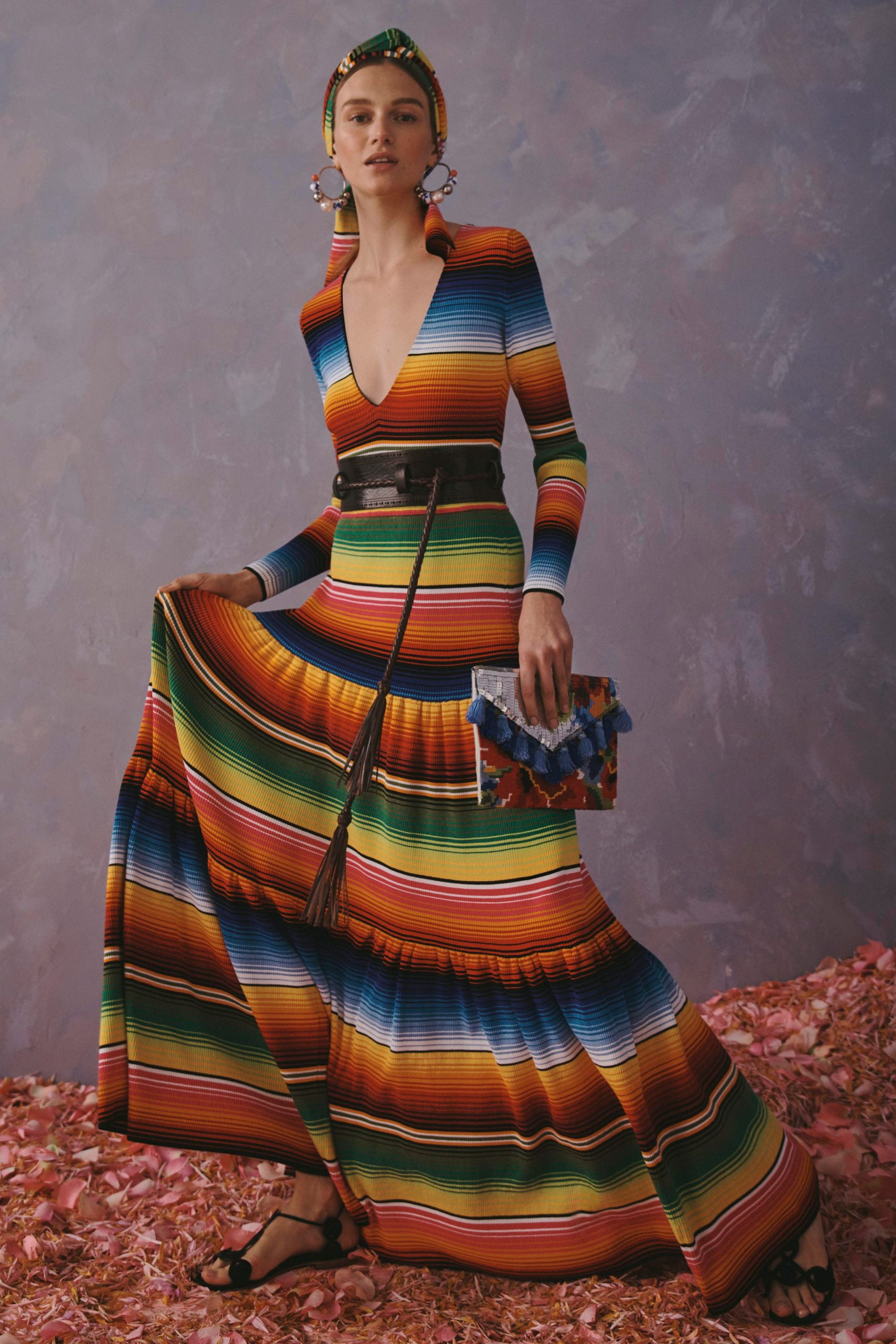 model wearing a dress with horizontal, multi-coloured stripes