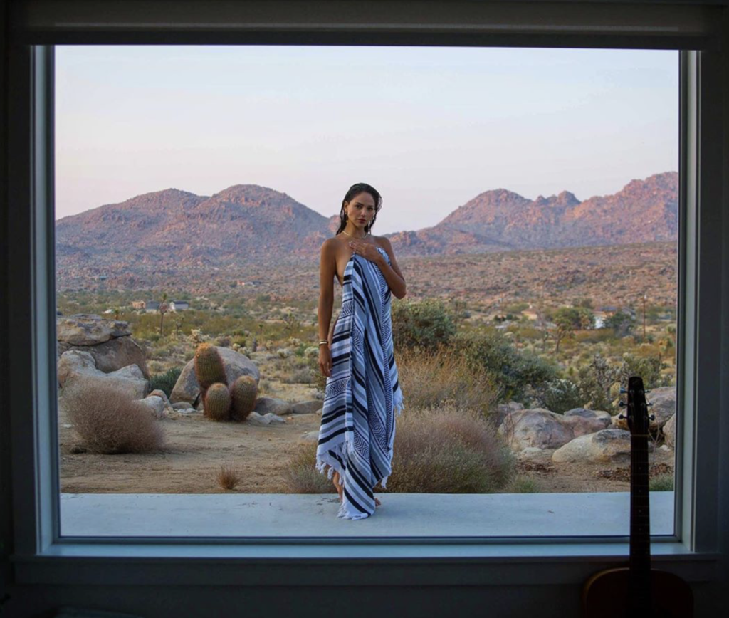 woman covering her body by holding a striped sarape in front of it, with a desert and mountains in the background