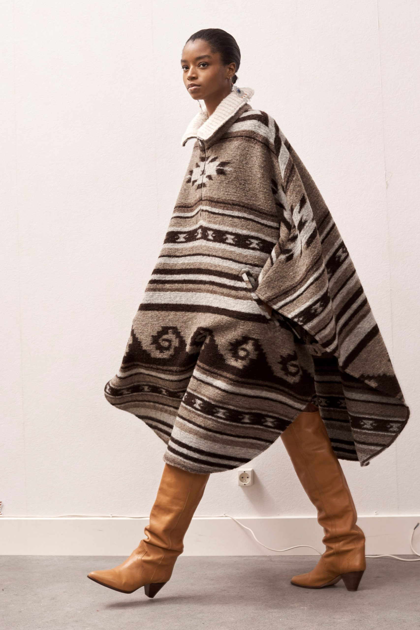 Model wearing a cape with stripes and undulating motifs in different shades of brown and caramel-colored, knee-length boots