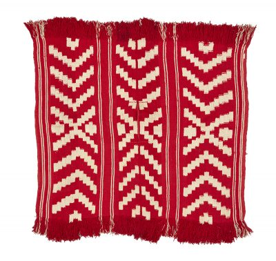 Photo of a squared textile with symmetrical chevron patterns of white color over a red ground