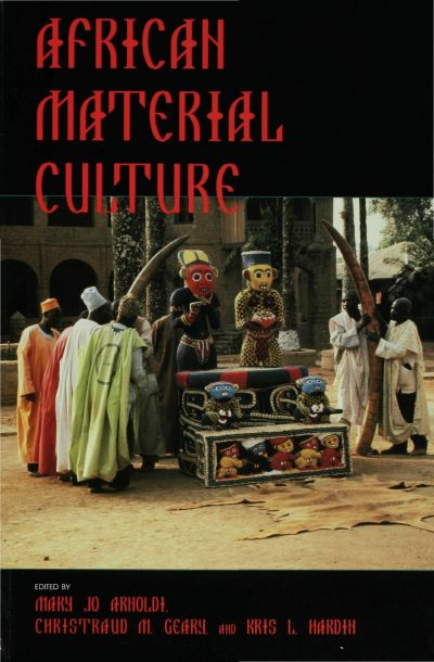 Book cover with froup of men and women wearing kaftans standing around a stand with small multi-coloured sculptures