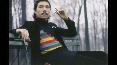 Photo of Antonio Lopez with shoulder-length haircut and a mustache, wearing a black T-shirt with multi-colored horizontal stripes, black trousers and cardigan, sitting on a park bench holding a cigarette in one hand and with trees with bare branches in the background