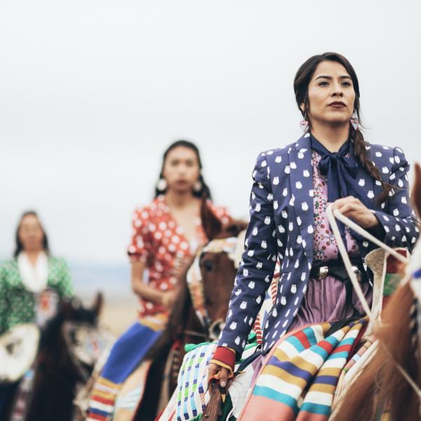 Image of row of women riding horses wearing fashionable Indigenous-designed clothing