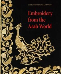 Book cover with close-up of embroidery with stylized bird and scrolling leaves of gold color on a black ground