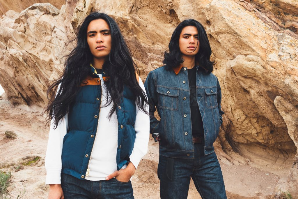 Two persons standing in front of rocks; one wears a white, long-sleeved top, a blue denim vest and blue jeans and the other onee wears matching denim jacket and trousers and a black T-shirt
