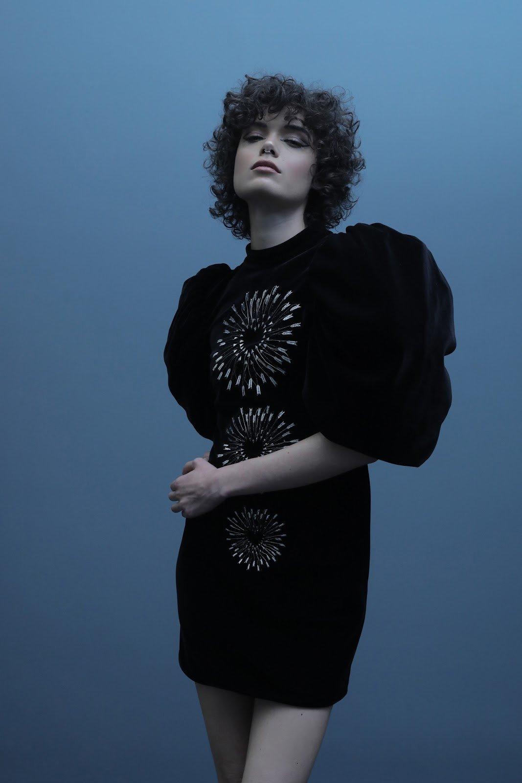 Model in black dress posing against blue background