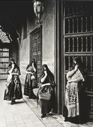 "Black-and-white photograph of ""tapadas limeñas"", the popular female figures from eighteenth- and nineteenth-century Lima that wore scarves around their head, leaving one eye uncovered"