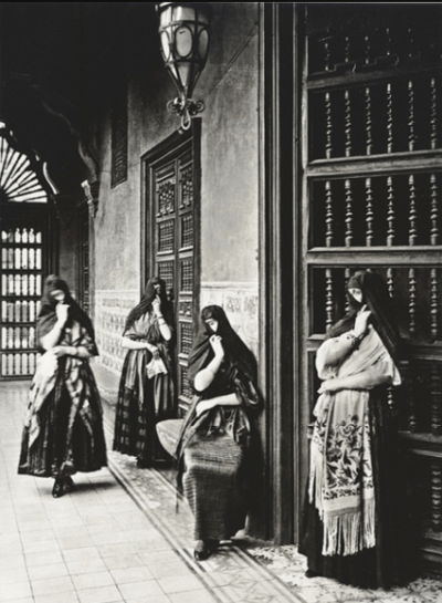 """Black-and-white photograph of """"tapadas limeñas"""", the popular female figures from eighteenth- and nineteenth-century Lima that wore scarves around their head, leaving one eye uncovered"""