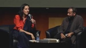 Photo of a woman holding a microphone to speak and a man sitting down with a coffee table in front