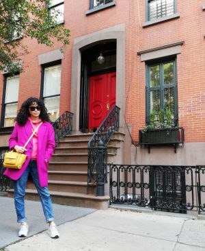 Woman wearing a bright pink coat, yellow handbag and blue jeans, posing in front of a red stone townhouse with steps leading to a red door