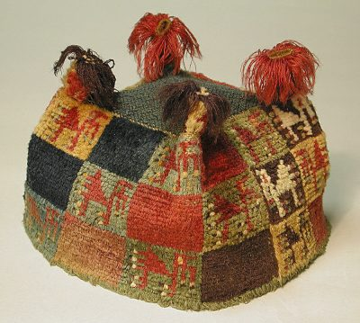 Image of a four-cornered Wari hat with checks of different colors, some of them featuring semi-abstract camelid figures