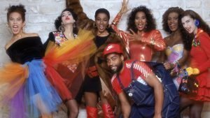 Image of models wearing multi-coloured dresses and a man with a red cap, red T-shirt, and blue denim overall towards the middle