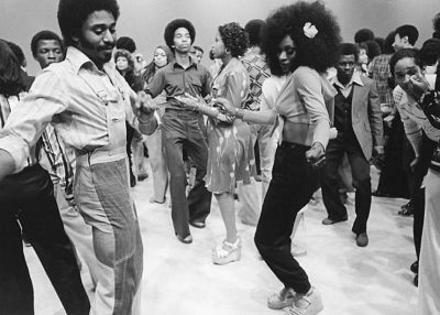 Black-and-white photo of group of people dancing in 70s fashion