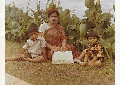Chopra, Prem Shil. Prem Lata Chopra in Madras. Photograph. Madras, India, 1970. Prem Lata Chopra sits in front of a garden with her children, wearing a sari.