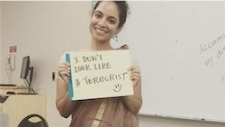 """Image of Dr. Tanya Rawal-Jindia wearing a sari and holding a sign that reads """"I don't look like a terrorist"""""""