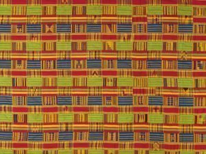 Textile with repetitive, abstract patterns made up of lines and stripes of green, blue, red, and orange color