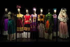 Photo of white mannequins dressed with Frida Kahlo's Tehuana-style outfits in a dark room