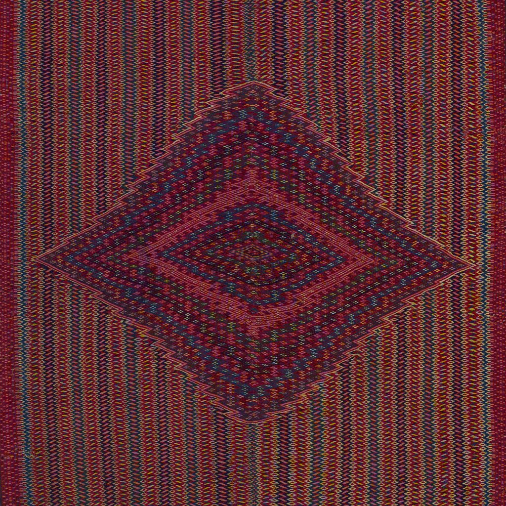 Close-up of a sarape with a central lozenge made up of zig-zagging lines of different colors and multi-colored stripes made up of alternating vertical zig-zagging lines and strips of lozenges