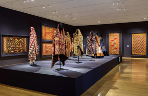 Gallery view with textiles hanging on the wall and a central platform with mannequins with mantles and dresses