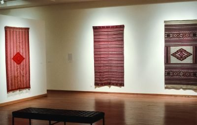 Gallery view with sarapes hanging on the walls