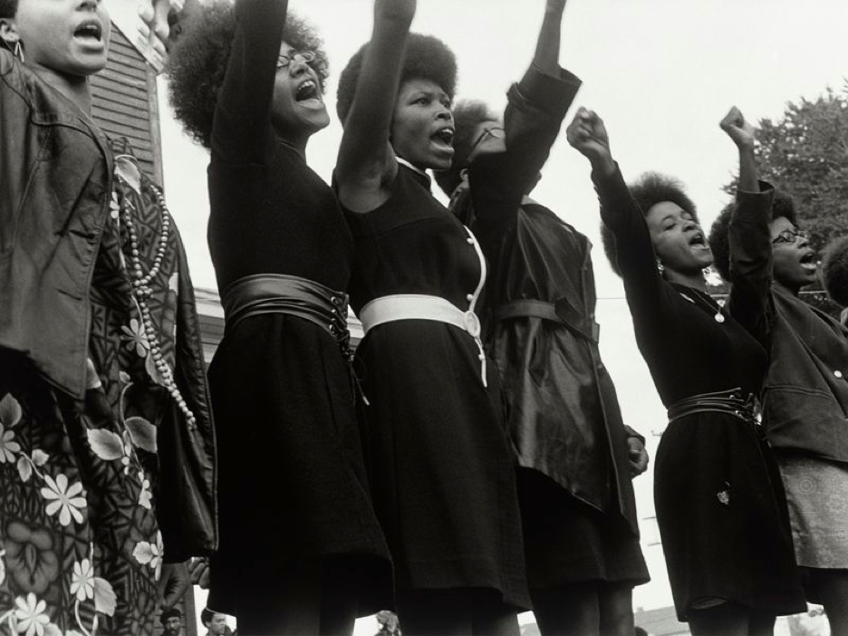 Black and white photo of 5 women with their fists raised