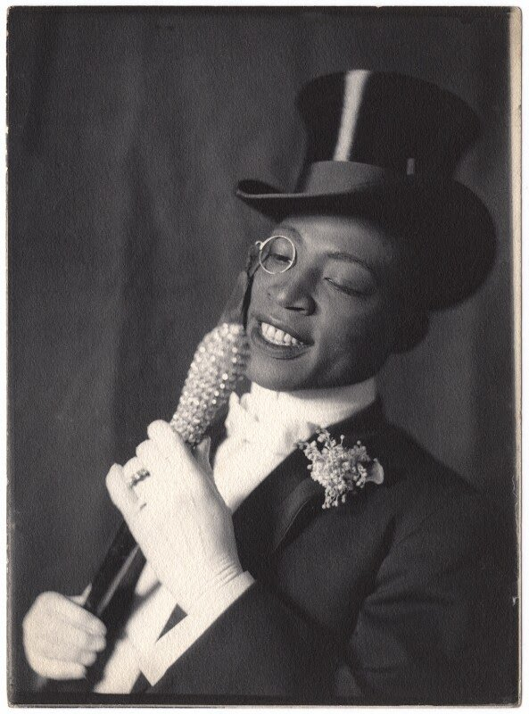 Black and white photo of man in full tuxedo, top hat, monocle, holding a bedazzled cane wearing white gloves.George W. Walker in 'In Dahomey'. By Cavendish Morton platinotype print, 1903.