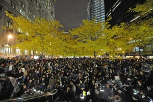 Photo of a group of people gathering in a part with trees and buildings in the background