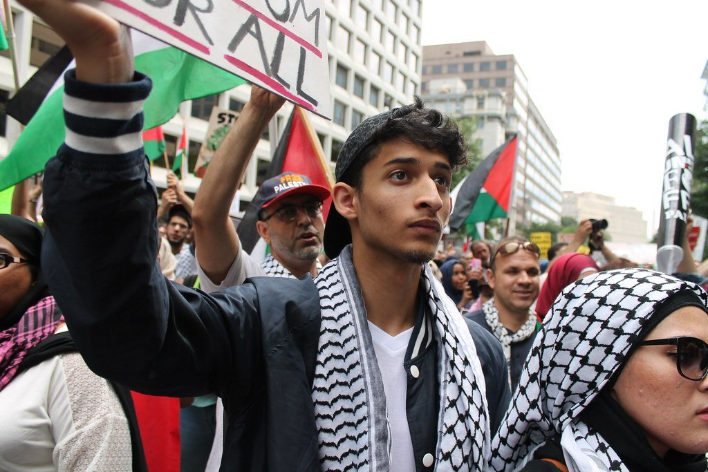 closeup on a few people among hundreds at a demonstration in support of Palestine; a young man holds up a protest sign