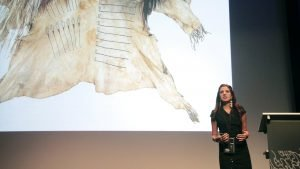 Photo of Jessica Metcalfe delivering her lecture and an image of a calfskin coat in the background