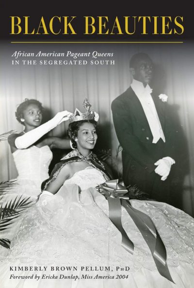 Black-and-white photo with two seated, black women in gowns, one putting a crown on the other's head, and a black man in a tuxedo standing at their side