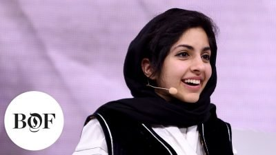 Photo of woman wearing a white shirt and black hijab with a microphone, giving a talk