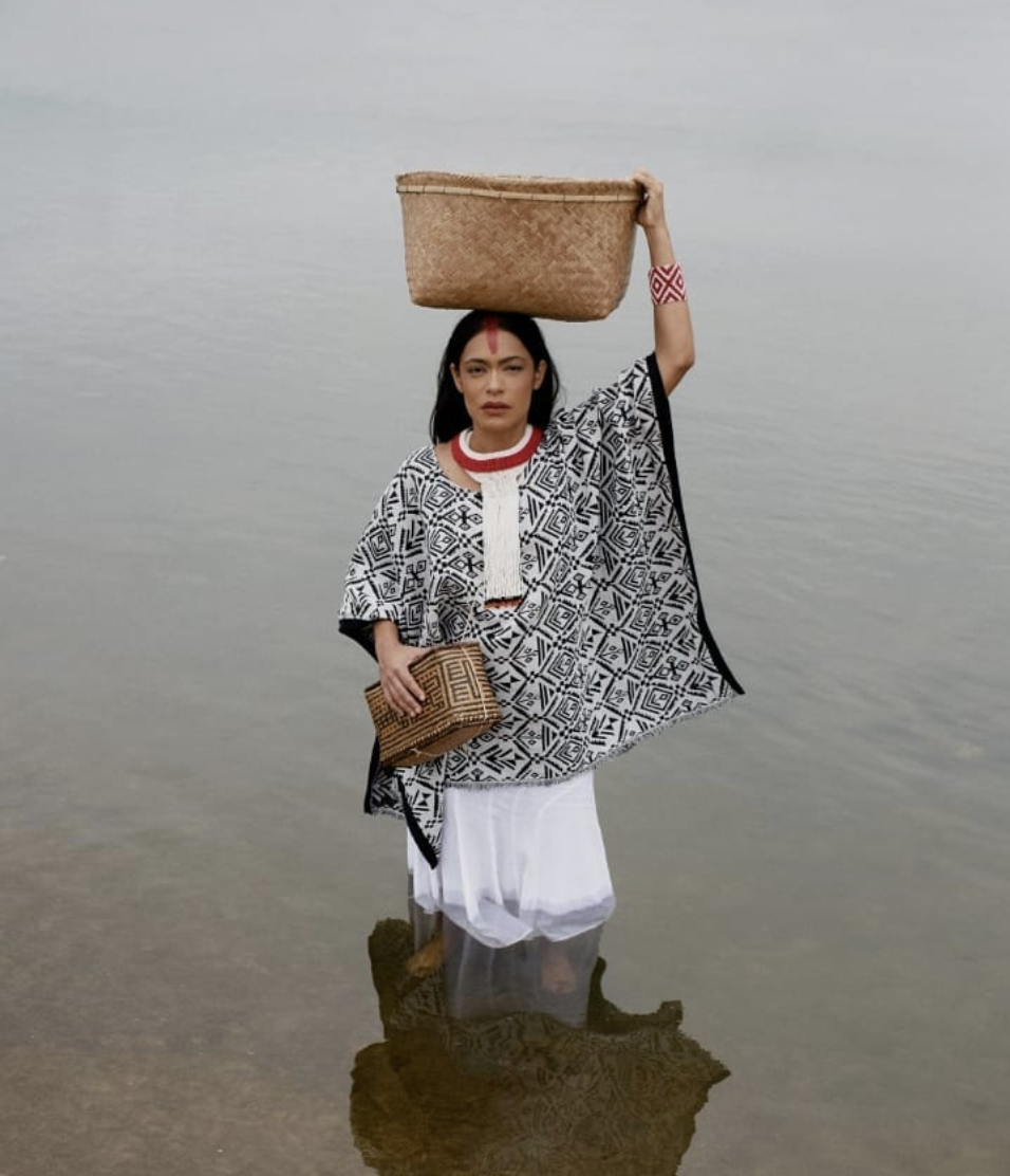 Brazilian indigenous woman standing in lake holding a woven basket on her head for a style editorial