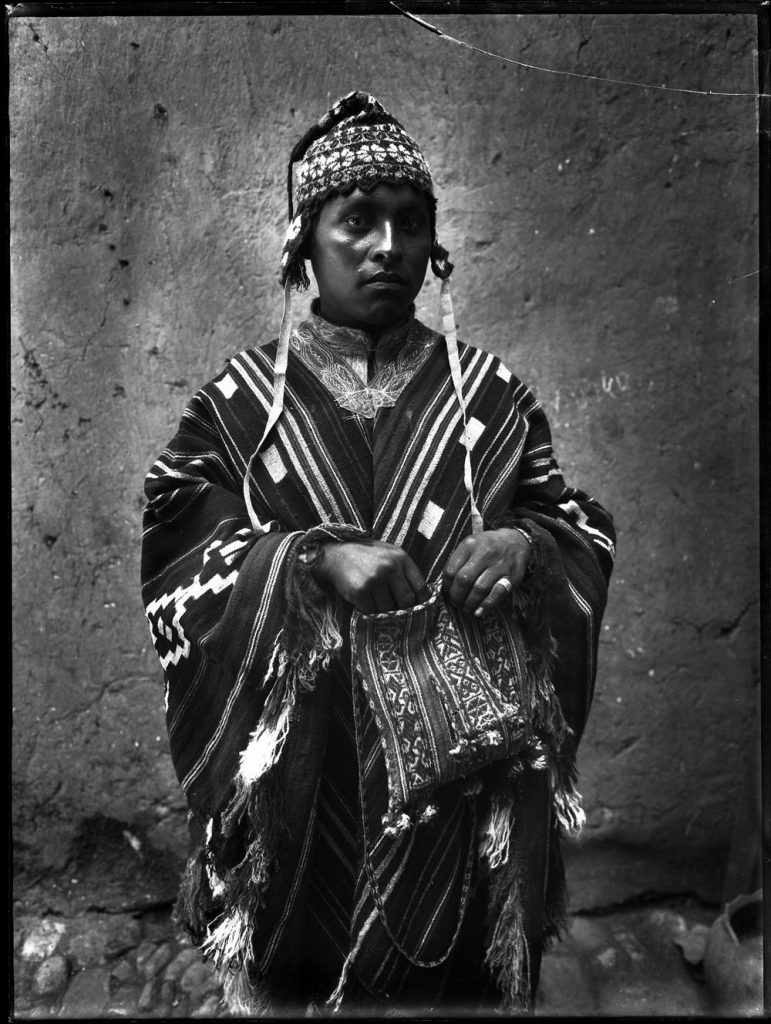 Black-and-white photo of a Peruvian countryman wearing a striped mantle, a knit hat, and carrying a ch'uspa