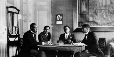 Photo of four black men wearing formal suits, sitting around a table