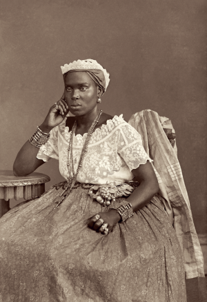 Photo of black woman wearing a white shirt, wide skirt, and accessories, sitting on a chair