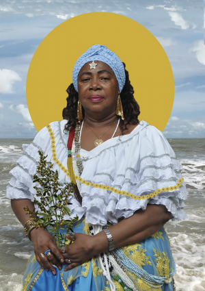 Photo of black woman wearing a white shirt, blue-and-yellow skirt, blue headband, and jewelry, and holding a bundle of flowers in her hands, with the sea and blue sky in the background