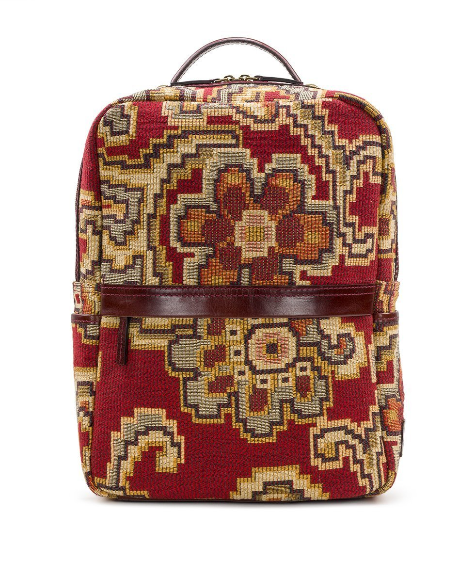 Photo of backpack with stylized floral motifs and a thin, brown zipper running horizontally through the middle