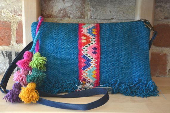 Photo of blue bag with strip with semi-abstract, multicolored motifs running down the center and a bundle of tassels on one side
