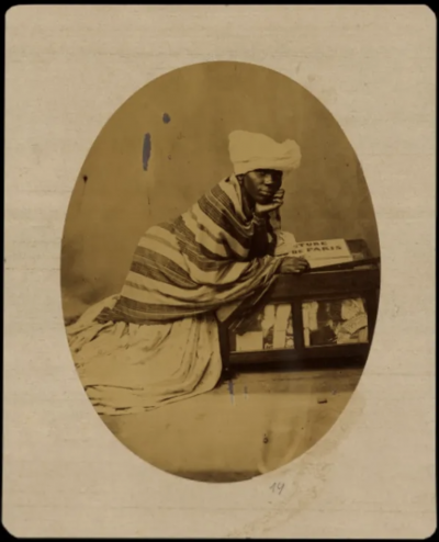 Photo of Black woman wearing a white headdress and a striped shawl over a white dress.