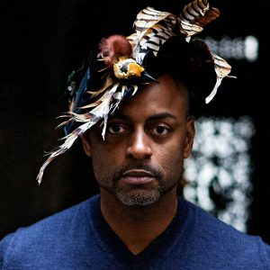 Photo of black man with a blue v-neck sweater and a feather headdress