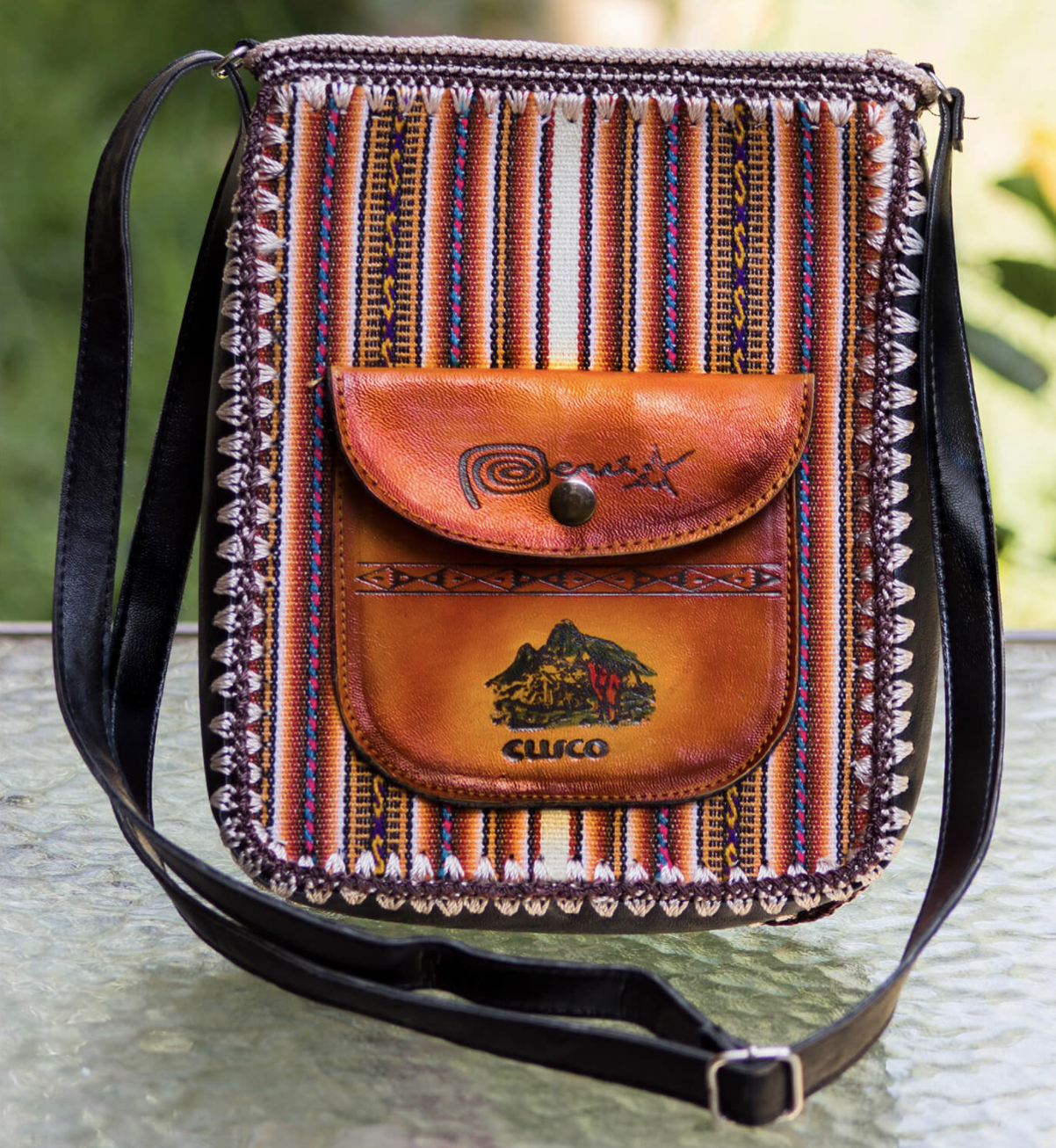 """Photo of bag made with a striped textile and a leather pocket with the words """"Peru"""" and """"Cusco"""" inscribed on the front"""