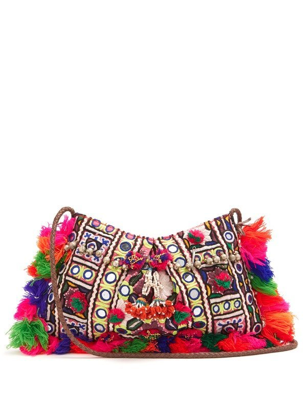 Photo of bag with pompoms, tassels, and embroidered with colored threads and small, round mirrors