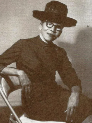Photo of woman wearing a black suit, hat and glasses