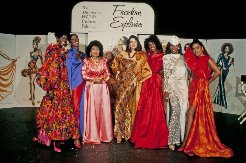 """Ebony Fashion Fair founder and director Eunice Johnson (in pink) stands with models during the 33rd annual Fashion Fair in 1991. Six models are seen along with Johnson in front of a sign that reads """"Freedom Explosion!"""""""