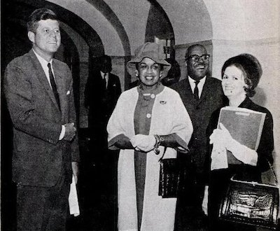 Fashion Fair director/editor Freda DeKnight (center) stands with President John F. Kennedy when the fashion fair models visited the White House.